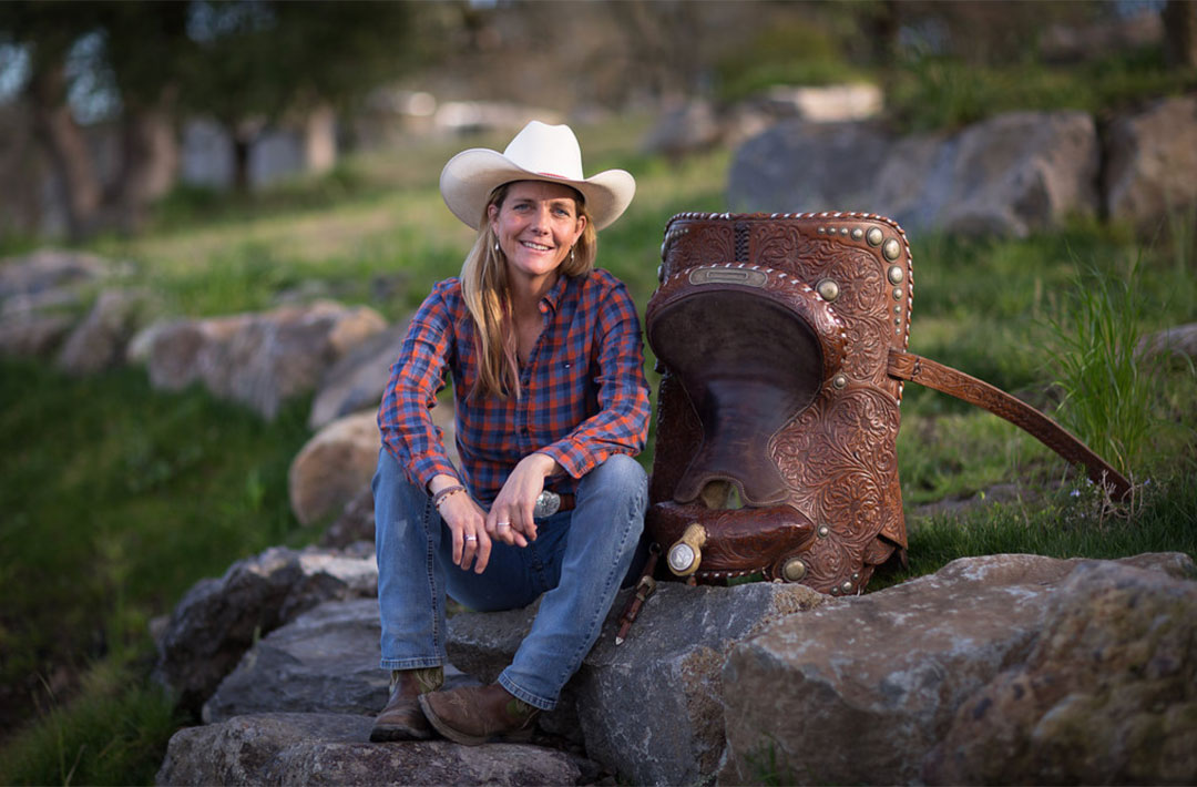 Picture of Michelle Rogers sitting on a rock with a saddle next to her